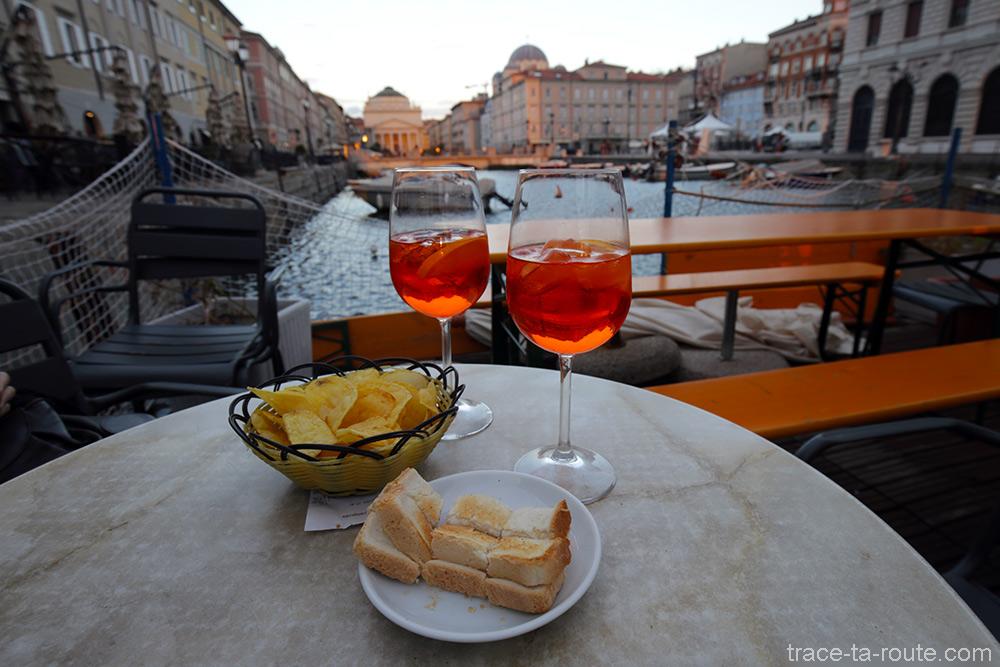 Aperitivo Aperol Spritz no terraço do Caffè Rossini no Grande Canal de Trieste com a Igreja de Sant'Antonio Nuovo ao fundo