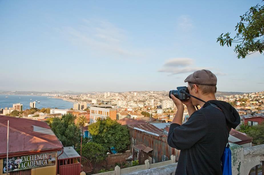 Turistas aproveitam a vista do Paseo 21 de Mayo para fotografar a cidade de Valparaíso de cima - há várias barracas de artesanato para turistas na rua estreita