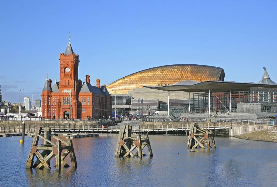 """Uma das vistas clássicas da cidade <strong>Cardiff</strong> é este edifício de paredes vermelhas no porto que foi originalmente construído para atender às necessidades do porto.  Em 1897, o edifício foi apelidado afetuosamente hoje """"Baby big ben""""É um museu.  Ao fundo está o moderno Millennium Stadium, outro marco local"""" class=""""lazyload"""" data-pin-nopin=""""true""""/></div> <p class="""