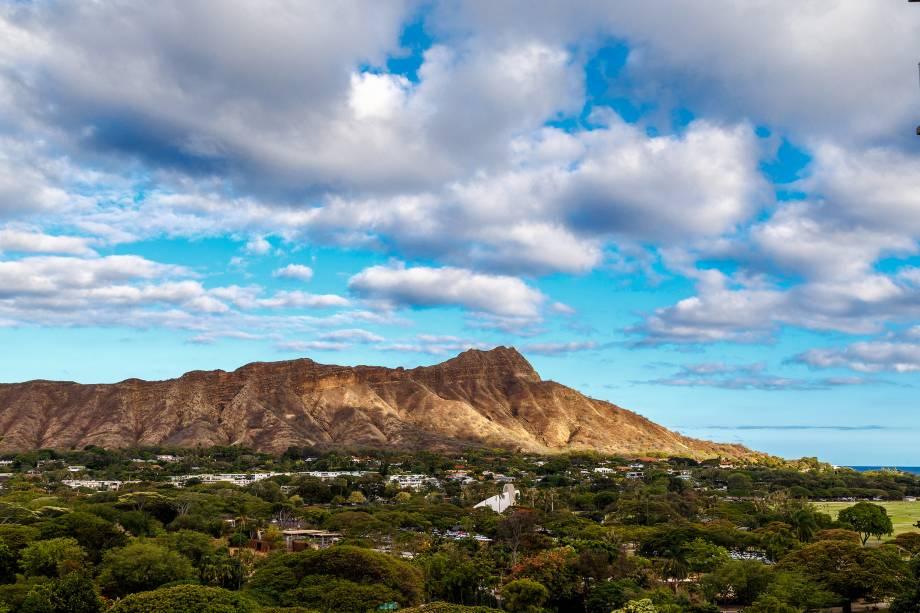 O extinto vulcão Diamond Head, no sudeste de Honolulu, domina o horizonte da cidade.  Se você subir 1300 pés de altura, terá uma vista panorâmica da ilha de Oahu