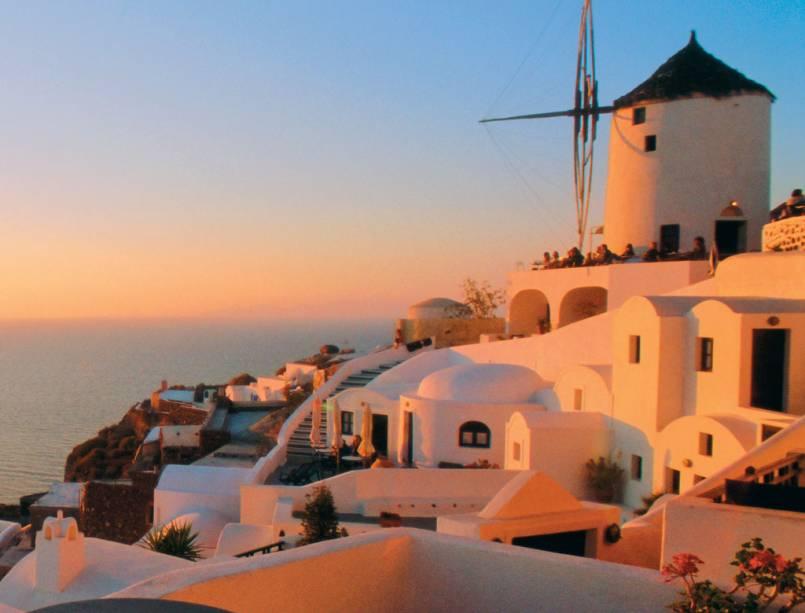 O sol busca seu lugar no Mar Egeu do lado de Oia em Santorini, Grécia