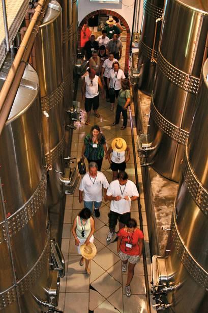 Os turistas e as cubas de inox onde fermentam os vinhos.  Atração da festa da colheita na vinícola Casa Valduga, Vale dos Vinhedos, em Bento Gonçalves