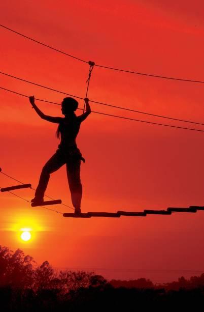 Mulher praticando uma travessia de desfiladeiro sobre cordas em um dos trechos da Verticália, em Brotas (SP), percurso composto por diversas modalidades de esportes radicais.
