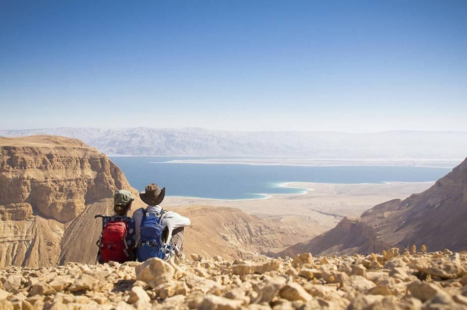 Um casal de viajantes observando o Mar Morto do topo de uma colina