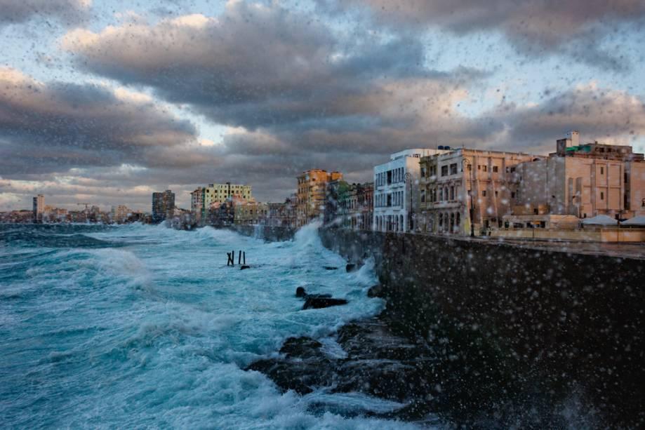 As muralhas centenárias do Malecón, a famosa orla marítima de Havana, protegem a cidade dos golpes do mar tempestuoso.  Em dias mais calmos, tanto os moradores quanto os turistas caminham na calçada.