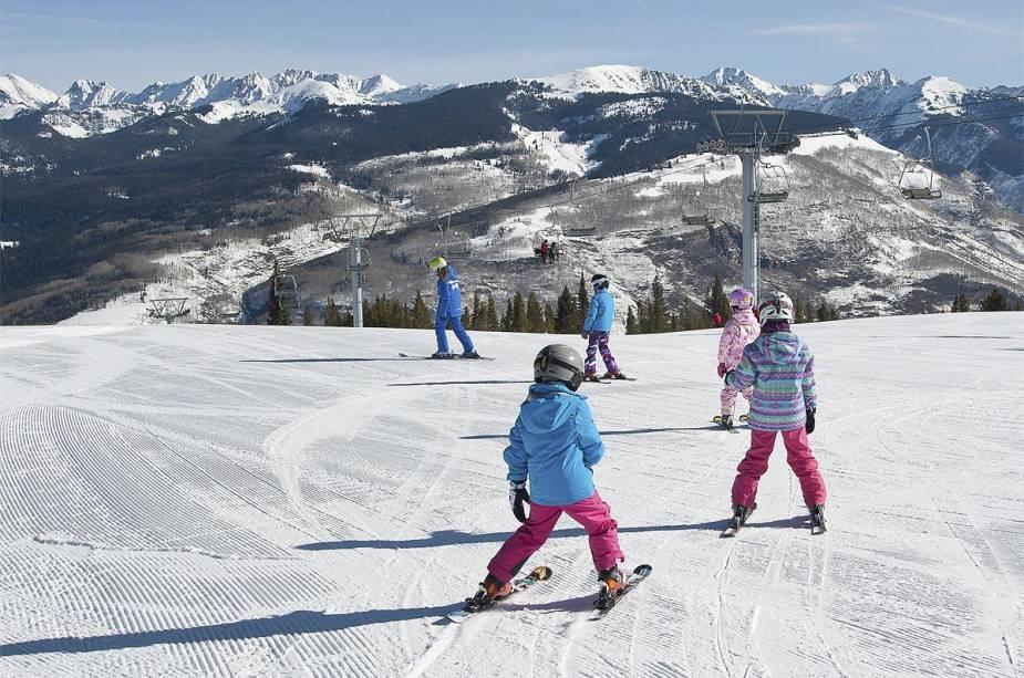 Crianças praticam seus primeiros esquis na neve