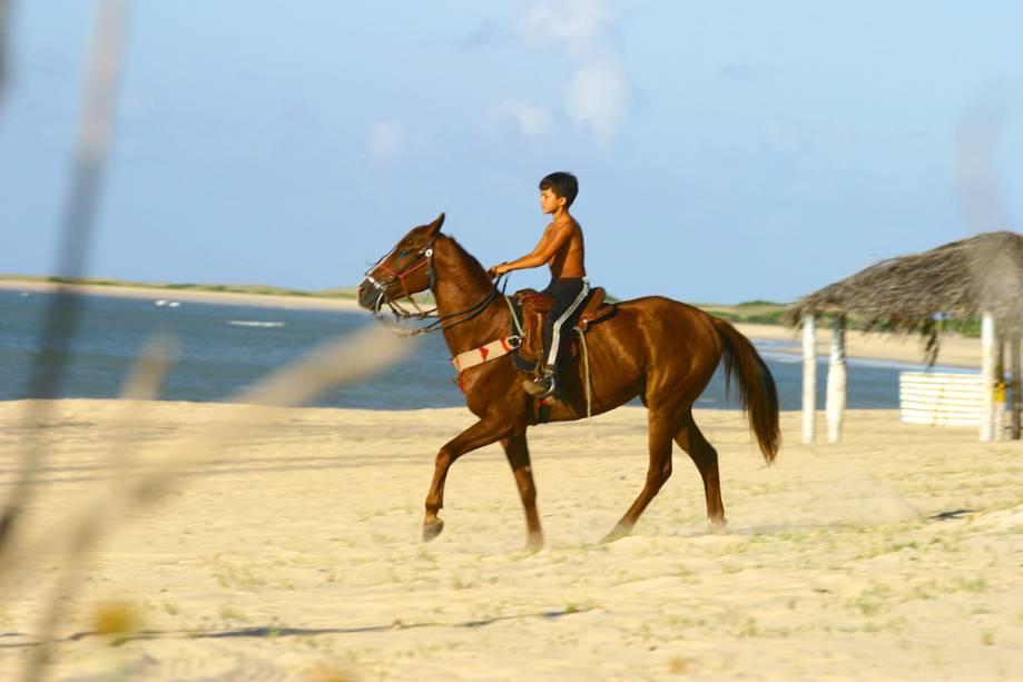 Menino andando a cavalo na praia de São Miguel do Gostoso