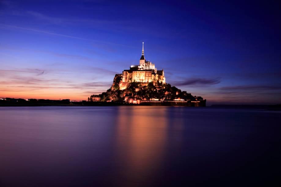 À noite, as luzes do castelo gótico e as paredes do Monte Saint-Michel na costa da Normandia induzem um estado de hipnose