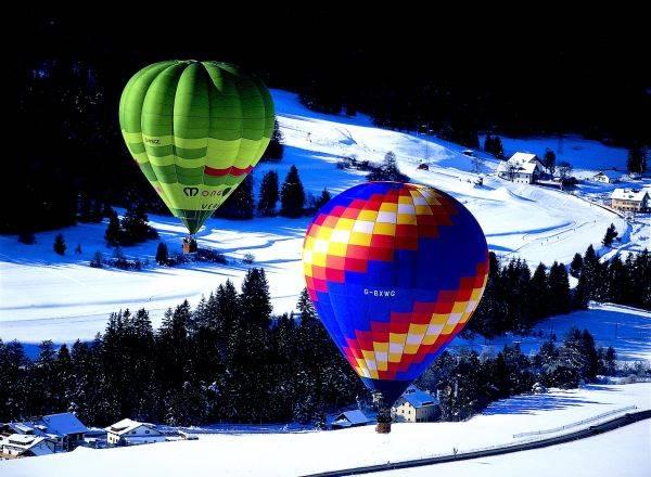 Os balões de ar quente sobem na magnífica paisagem de Val Gardena.  Ao retornar do passeio, você pode esperar pratos saudáveis e suculentos à base de batata, caça e porco, chucrute e cevada, refletindo a influência das vizinhas Áustria e Suíça.