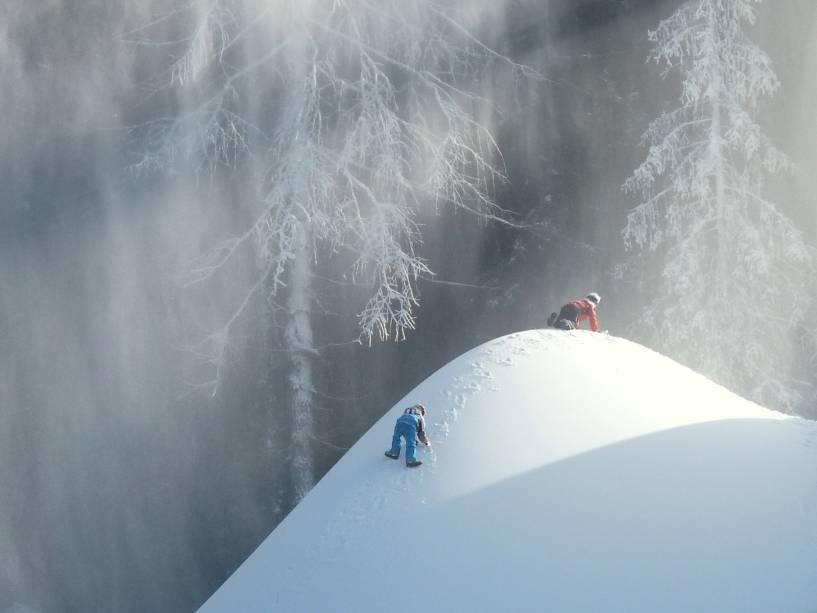 Crianças brincam em um monte de neve em Val Gardena