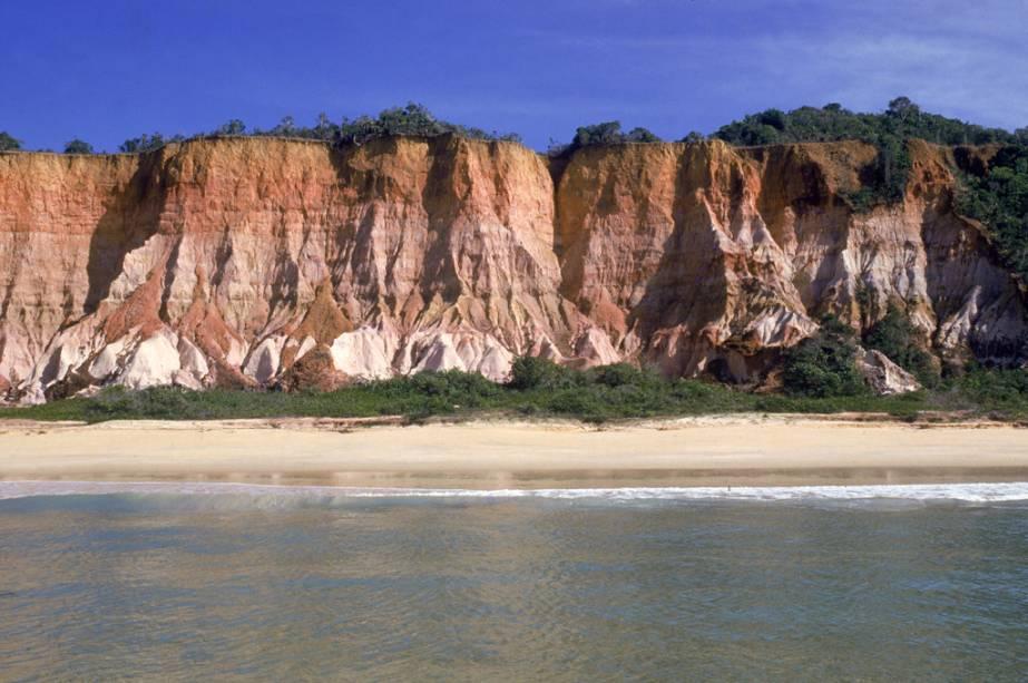 A Praia da Pitinga é versátil, no canto esquerdo há tendas que garantem movimento, no outro as falésias dominam a paisagem, o deserto e o mar calmo.