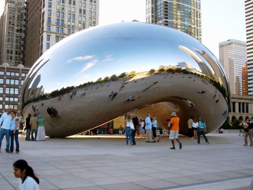 """O Cloud Gate é uma grande estrutura de metal polido projetada por Anish Kapoor.  Por razões óbvias, a escultura da AT&T Square no Millennium Park ganhou o apelido """"o feijão"""", Feijões"""