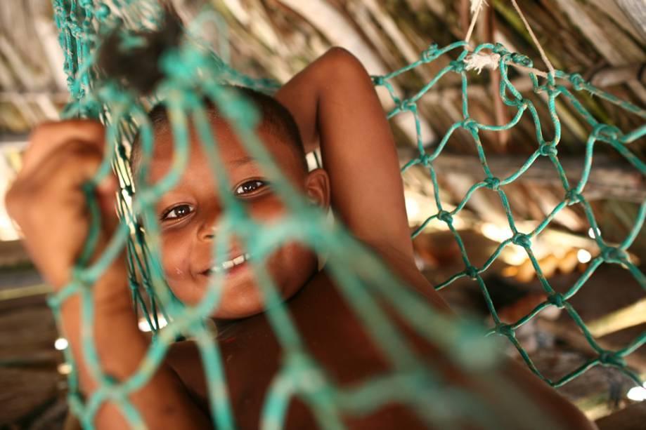 O menino descansa na sombra nos Lençóis Maranhenses.  A cada visita o visitante deve trazer protetor solar, chapéu, óculos escuros e água, pois o sol forte atinge a área