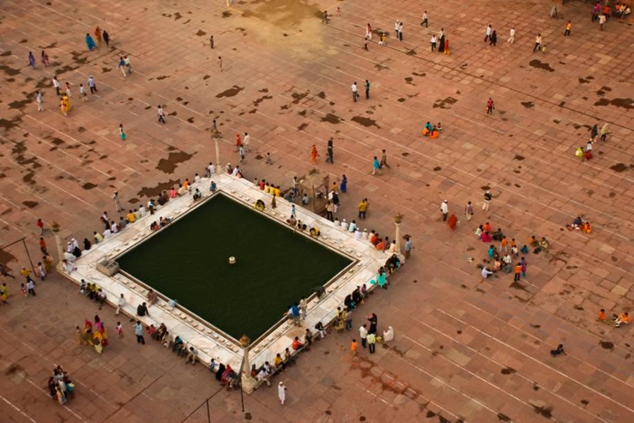 Pátio da mesquita Jama Masjid com fiéis realizando suas abluções cerimoniais