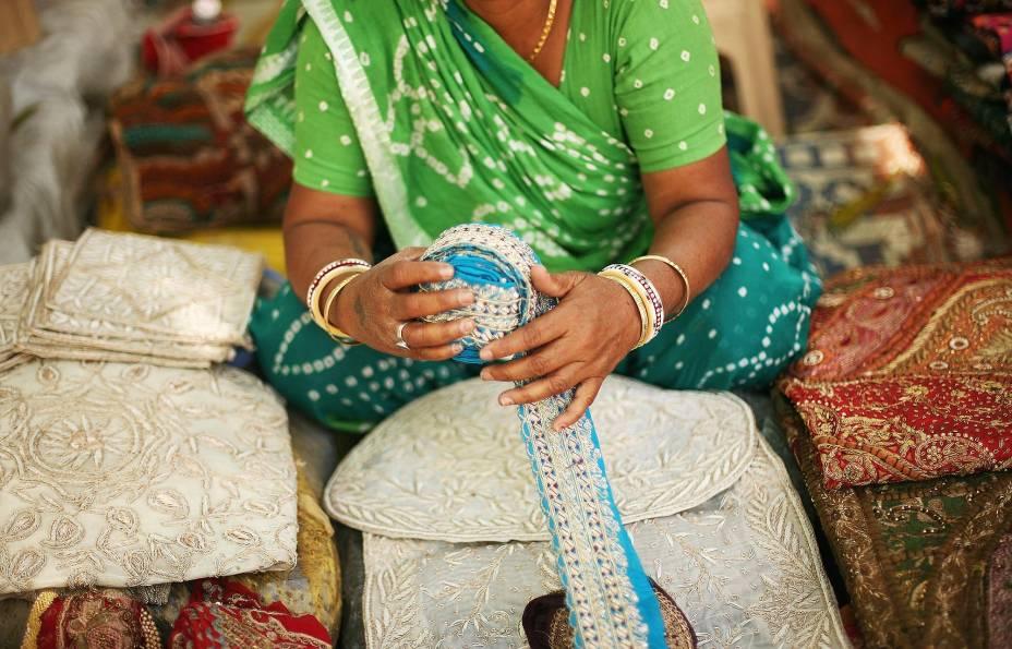 Mulher vende seda no mercado em Delhi, Índia