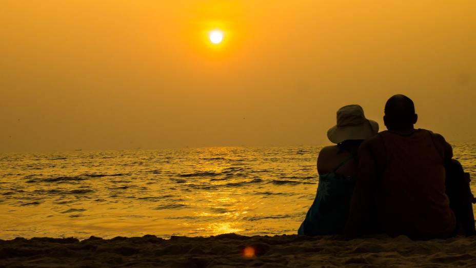 Casal assistindo ao pôr do sol na praia em Goa, Índia