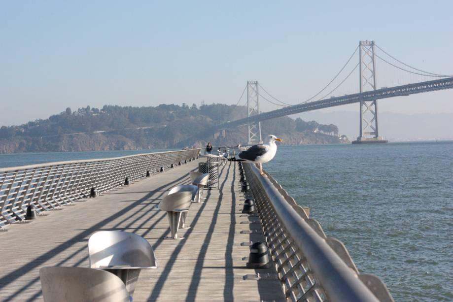 O calçadão leva a um mirante na costa de São Francisco.  Ao fundo, a Bay Bridge
