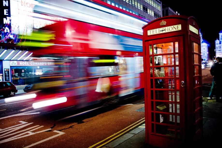 O lendário Routemaster, um ônibus vermelho de dois andares, passa por trás de outro marco de Londres: as cabines telefônicas vermelhas!