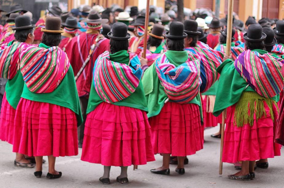 Mulheres indígenas se reúnem para protestar nas ruas de La Paz, Bolívia.  Cada região do país tem seus povos indígenas e cada povo tem seus próprios hábitos de vestir.  Na capital, por exemplo, as mulheres costumam usar saias leves e muito claras e chapéus pretos na cabeça.  Por dentro, o chapéu dá lugar a longas e elaboradas tranças