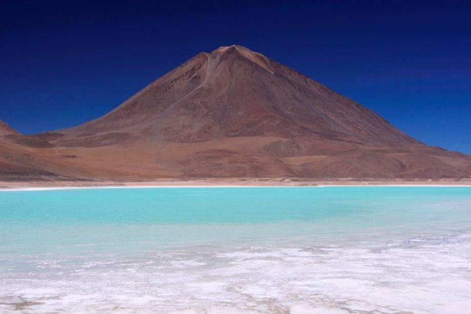 Laguna Verde fica a 4.000 metros de distância e tem esse tom devido a vestígios de cobre oxidado.  O vulcão Licanbur é um dos muitos que moldam o planalto boliviano