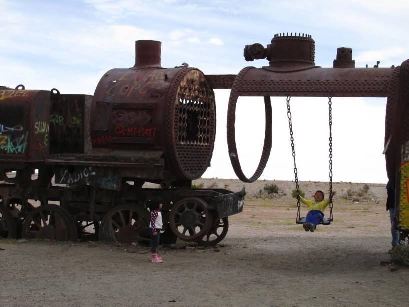 Crianças brincam no cemitério de trens em Uyuni, Bolívia