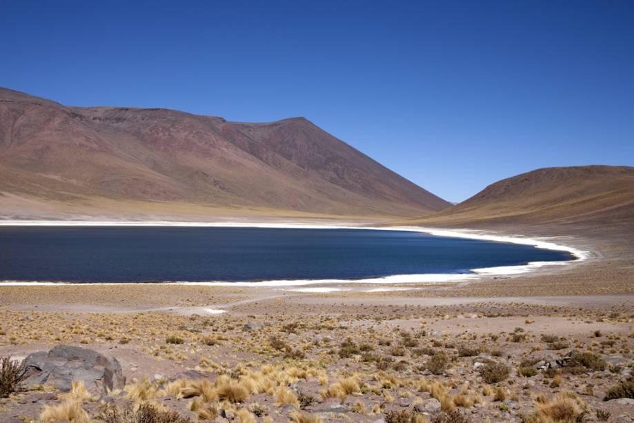 O contraste entre as cores da areia, a vegetação rala, o verde das águas das lagoas Meñiques e Miscanti e os picos nevados ao fundo convidam a meditar