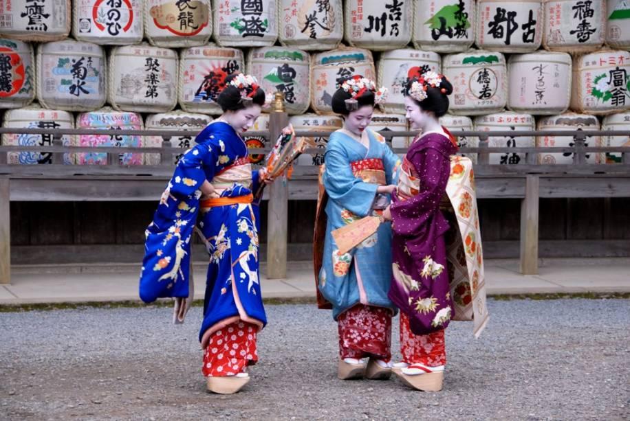 Gueixas aprendizes conhecidas como maiko se vestem com quimonos coloridos no Santuário Kyats Matsuo Taisha.  No fundo, tambores de saquê como oferendas.