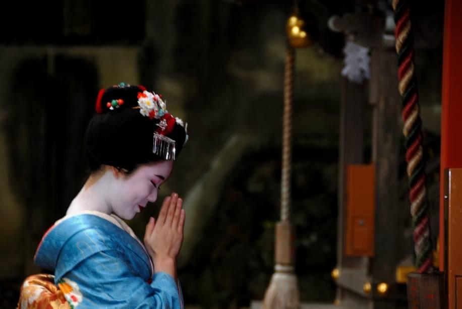 A aprendiz de gueixa conhecida como maiko ora no santuário Shinto Matsuo Taisha em Kyoto