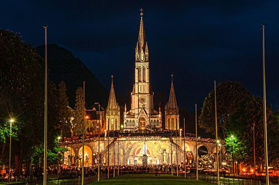 Procissões à luz de velas costumam acontecer em Lourdes, França, nas noites de verão