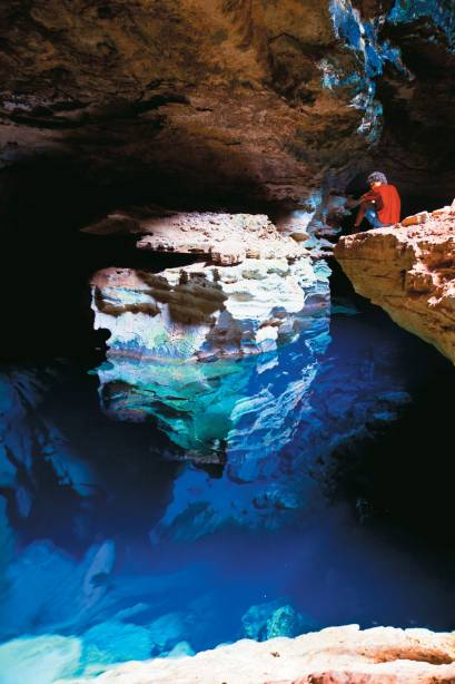 Poço Azul na caverna do Parque Nacional da Chapada Diamantina.  Quando atingem a água, os raios de sol mostram diferentes tons de azul e belas formações rochosas