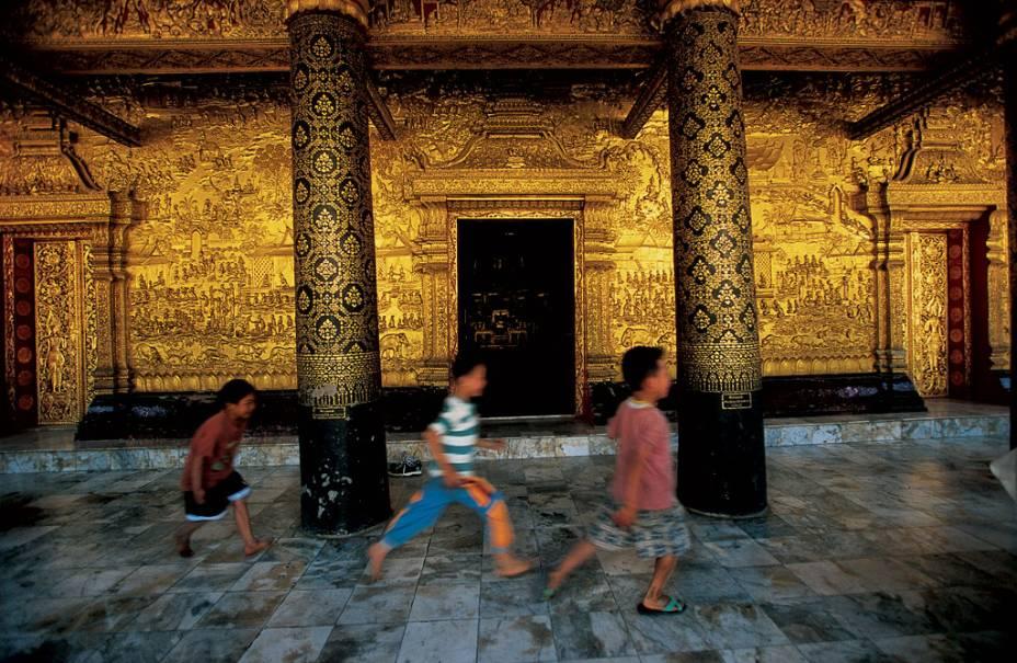 Os meninos, acostumados com a bela paisagem, passam correndo pelas paredes douradas de Wat Mai, um templo do século 18 adornado com cenas detalhadas da vida de Buda.  A designação como Patrimônio Mundial abrange toda a vila de Luang Prabang, uma antiga capital real