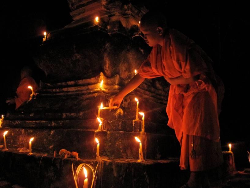 Um monge aprendiz acende uma vela durante a Boun Ok Phansa FEstiva em Luang Prabang
