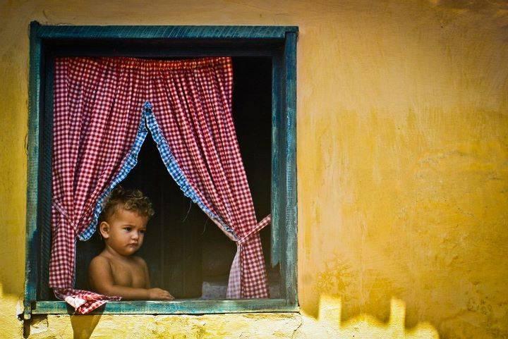 Uma mulherzinha nordestina na janela de sua casa em Canoa Quebrada (CE)