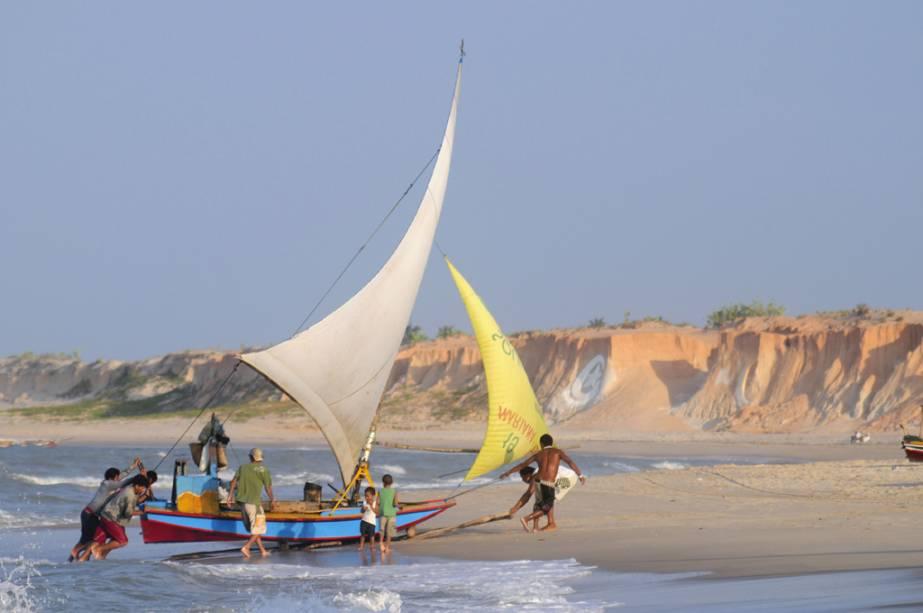 As falésias que mudam de tom e enfeitam a orla dominam o visual da Praia de Canoa Quebrada (CE).  Atrás delas, as dunas criam um bom contraste