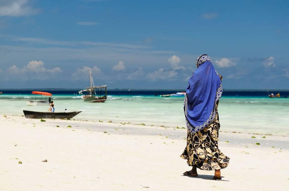 Muçulmano caminha na praia em Zanzibar