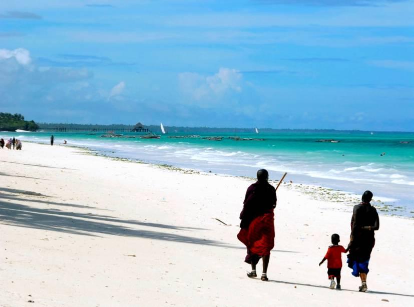 Família Maasai caminha na praia de Kiwengwa em Zanzibar, um arquipélago da Tanzânia no Oceano Índico
