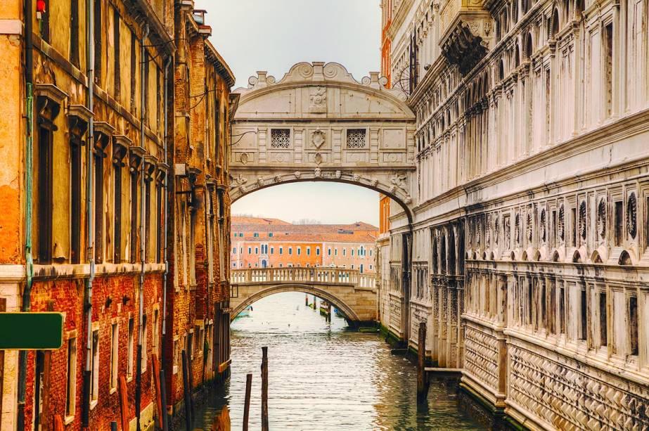 """A famosa Ponte dos Suspiros em Veneza servia de passagem entre os tribunais venezianos e a prisão - é chamada de Ponte dos Suspiros porque é o último local de onde o condenado teria uma vista da cidade em frente à prisão.  Você pode cruzar a ponte e se sentir como um condenado ao visitar o""""http://viajeaqui.abril.com.br/estabelecimentos/italia-veneza-atracao-palazzo-ducale"""" rel =""""Palácio ducal"""" Objetivo =""""_vazio""""> Palácio Ducal"""" class=""""lazyload"""" data-pin-nopin=""""true""""/></div> <p class="""