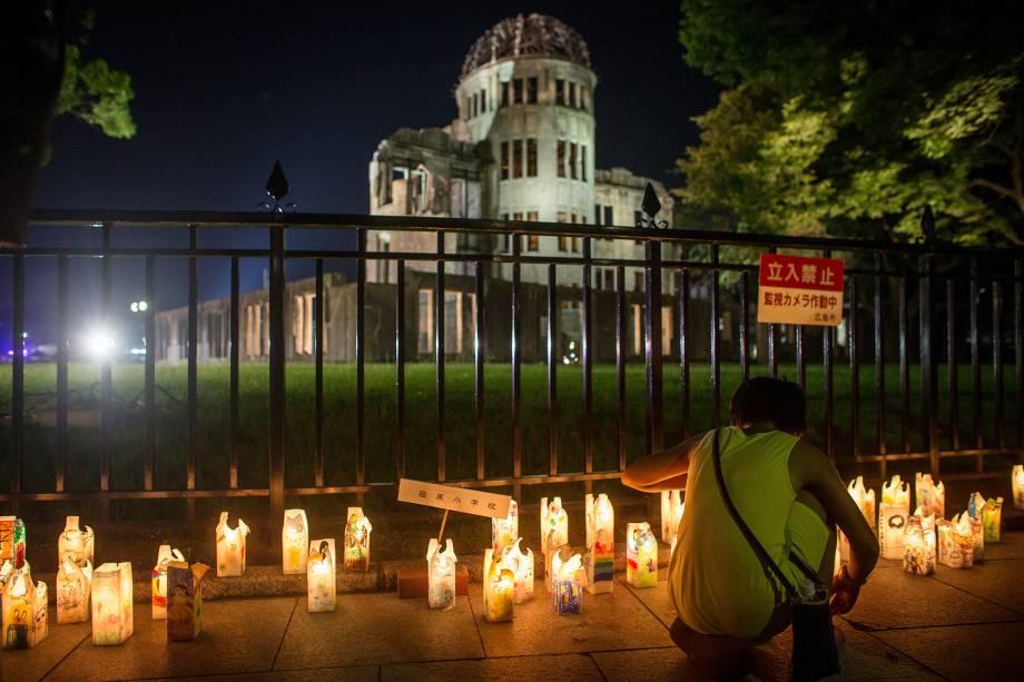 Uma menina acende velas em frente à catedral, que retrata o passado trágico da cidade quando foi destruída pelo primeiro bombardeio atômico da história em 6 de agosto de 1945
