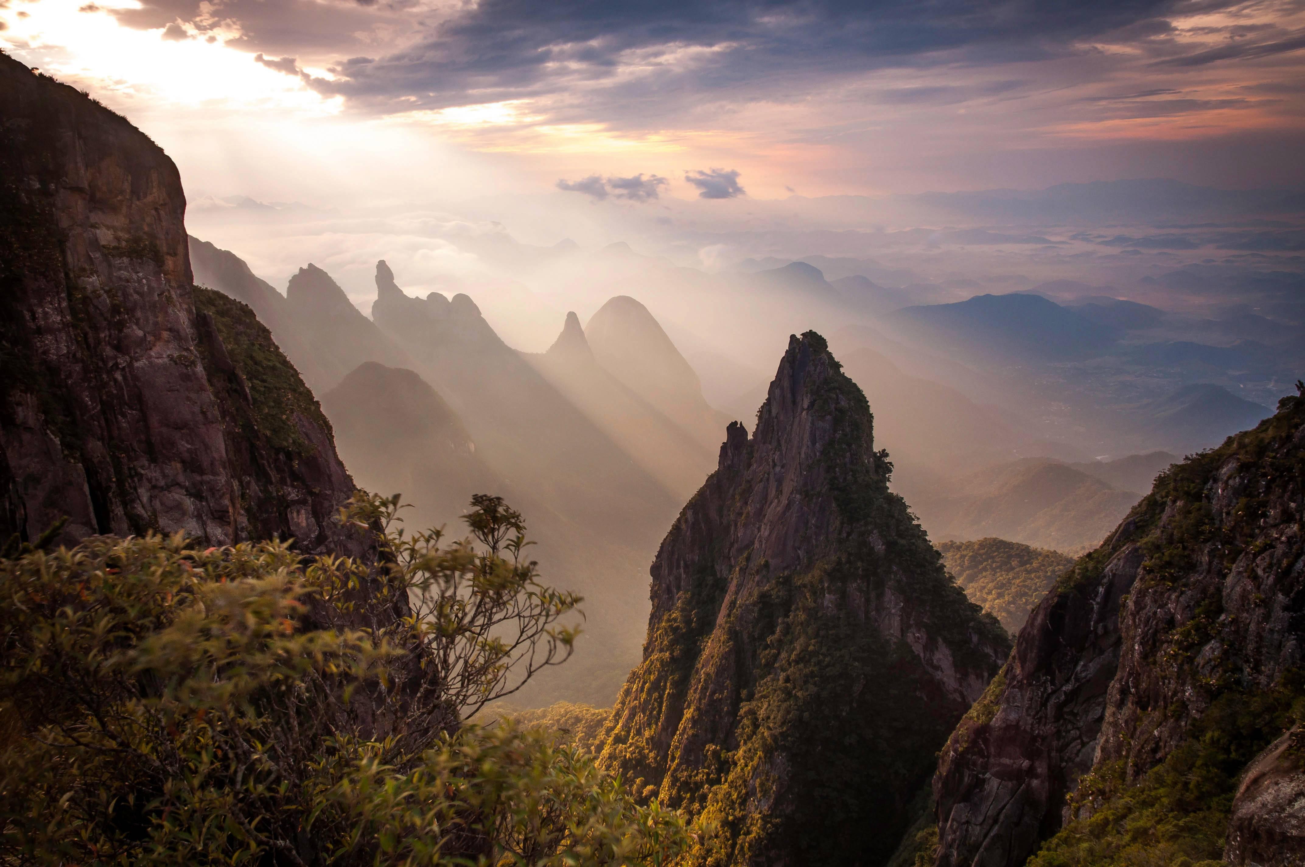 Formações rochosas e o cume do Dedo de Deus ao fundo no Parque Nacional da Serra dos Órgãos, no estado do Rio de Janeiro.
