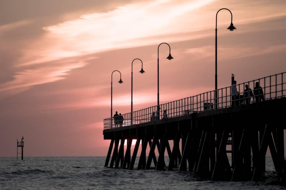 As pessoas assistem ao pôr do sol no Píer Glenelg, na cidade australiana de Adelaide