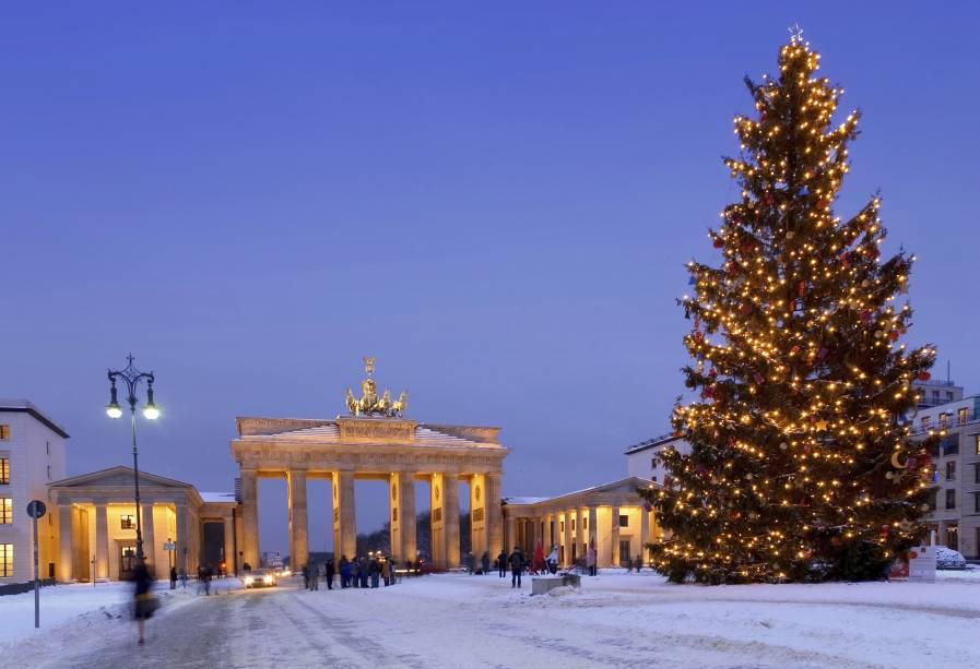 No final do ano, o inverno chega a Berlim com neve.  na foto, o Portão de Brandemburgo ao lado de uma enorme árvore de Natal