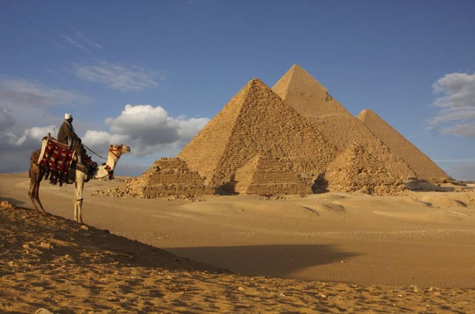 Beduínos e dromedários no planalto de Gizé.  É necessário cuidado para os visitantes, as pirâmides estão anexadas aos arredores do Cairo