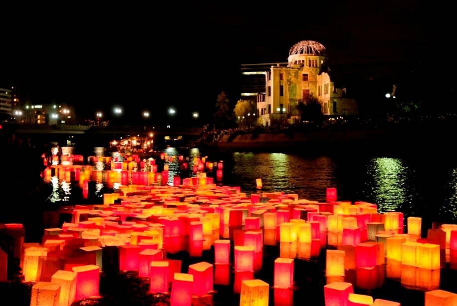 Lanternas com mensagens de paz no rio Ota.  Ao fundo, a cúpula da bomba de Hiroshima