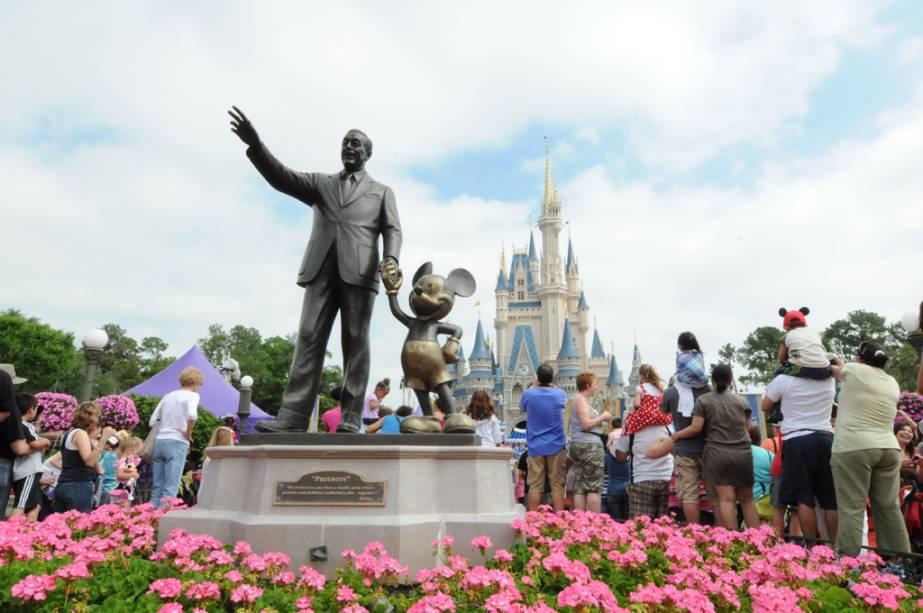 Estátua de Walt Disney com o castelo do Mickey Mouse e da Cinderela ao fundo no parque temático Magic Kingdom