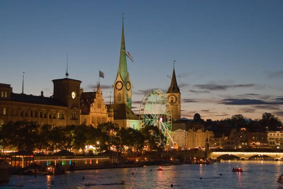 Visão noturna das igrejas de Fraumünster e São Petersburgo do Limmat em Zurique