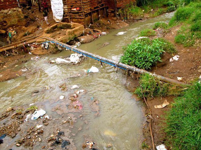 O sistema de água passa em frente aos esgotos a céu aberto de Kibera